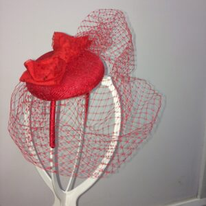 Red fascinator on headband with birdcage netting